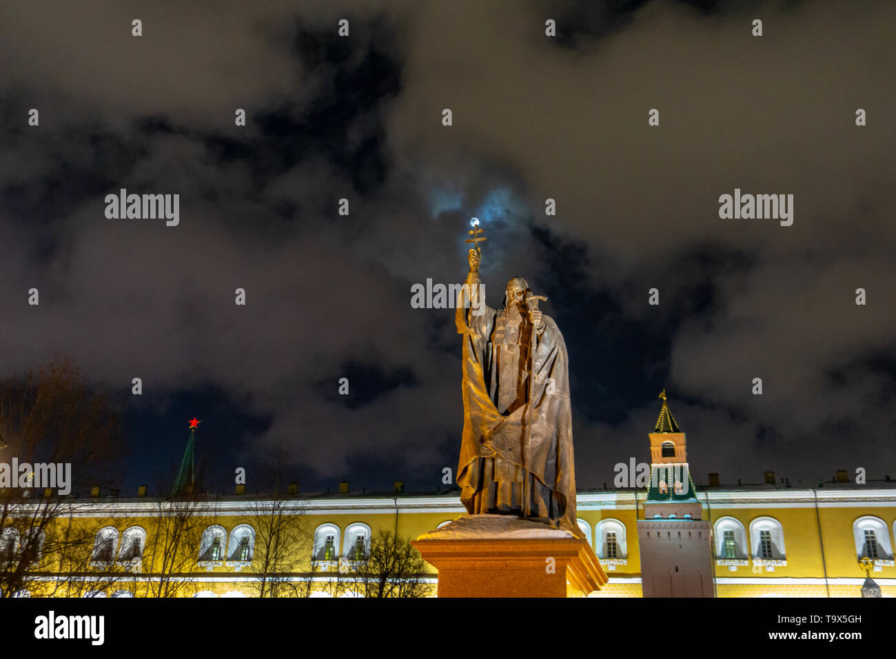 Saint statue with holding cross and on which moon shines, cloudy winter night sky, near Kremlin in Moscow - Stock Image