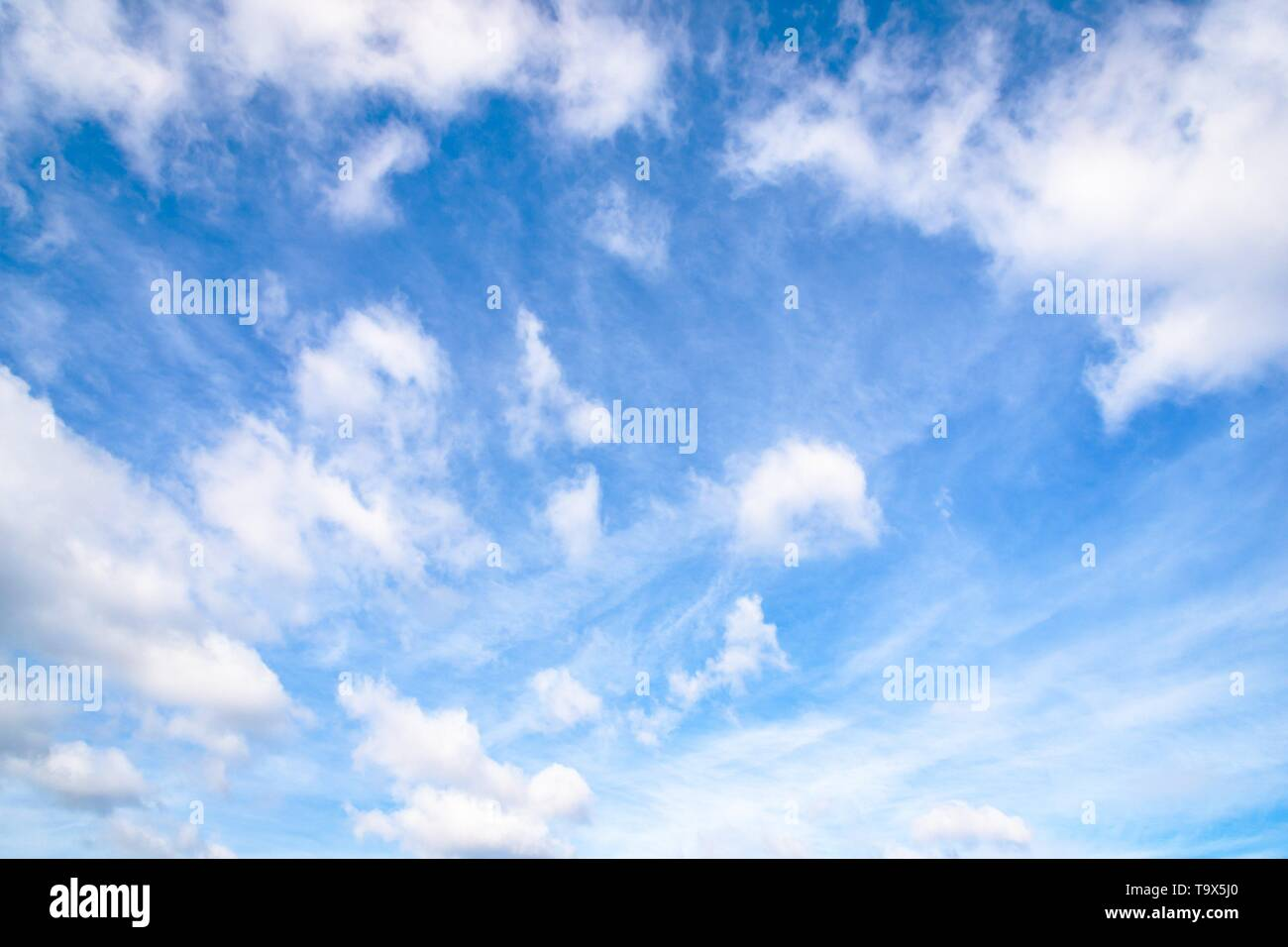 Beautiful white fluffy and cirrocumulus clouds on a blue sky background - Stock Image
