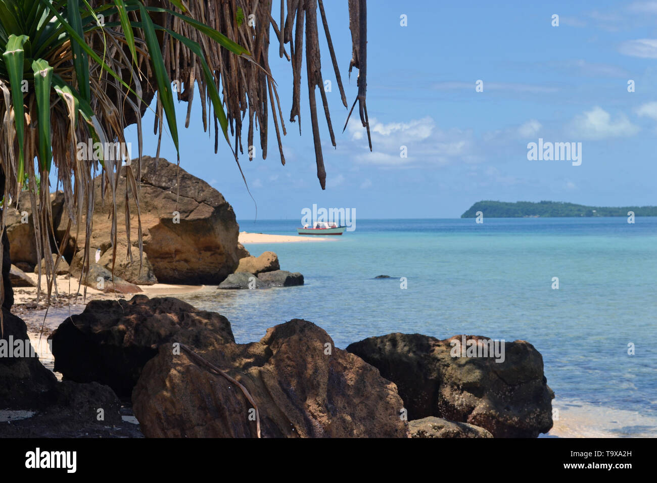 Boat and rocks on a beach in the Nukuatea motu, Wallis Island, Wallis & Futuna, South Pacific - Stock Image