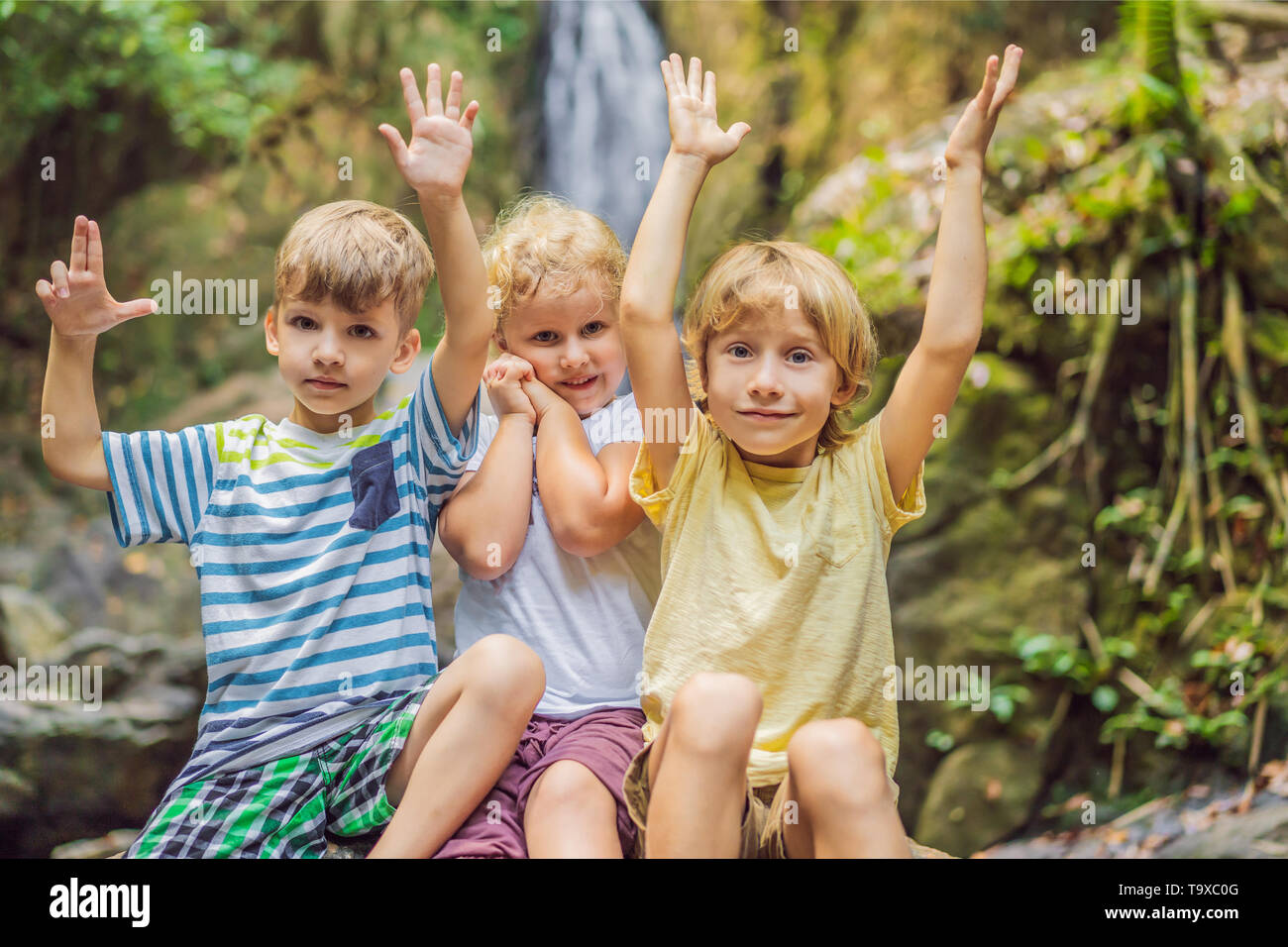 Children rest during a hike in the woods - Stock Image