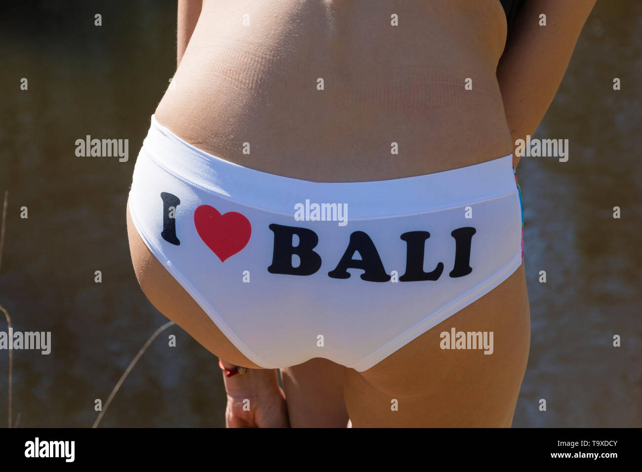 White swim trunks with an inscription I love Bali on a young slim girl. - Stock Image