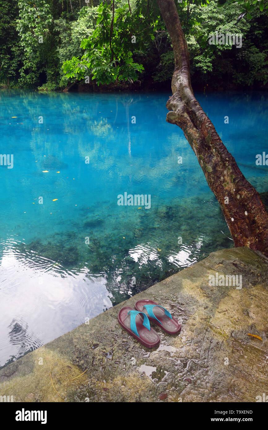 Shoes beside RiRi blue hole, Espiritu Santo, Vanuatu. No PR - Stock Image