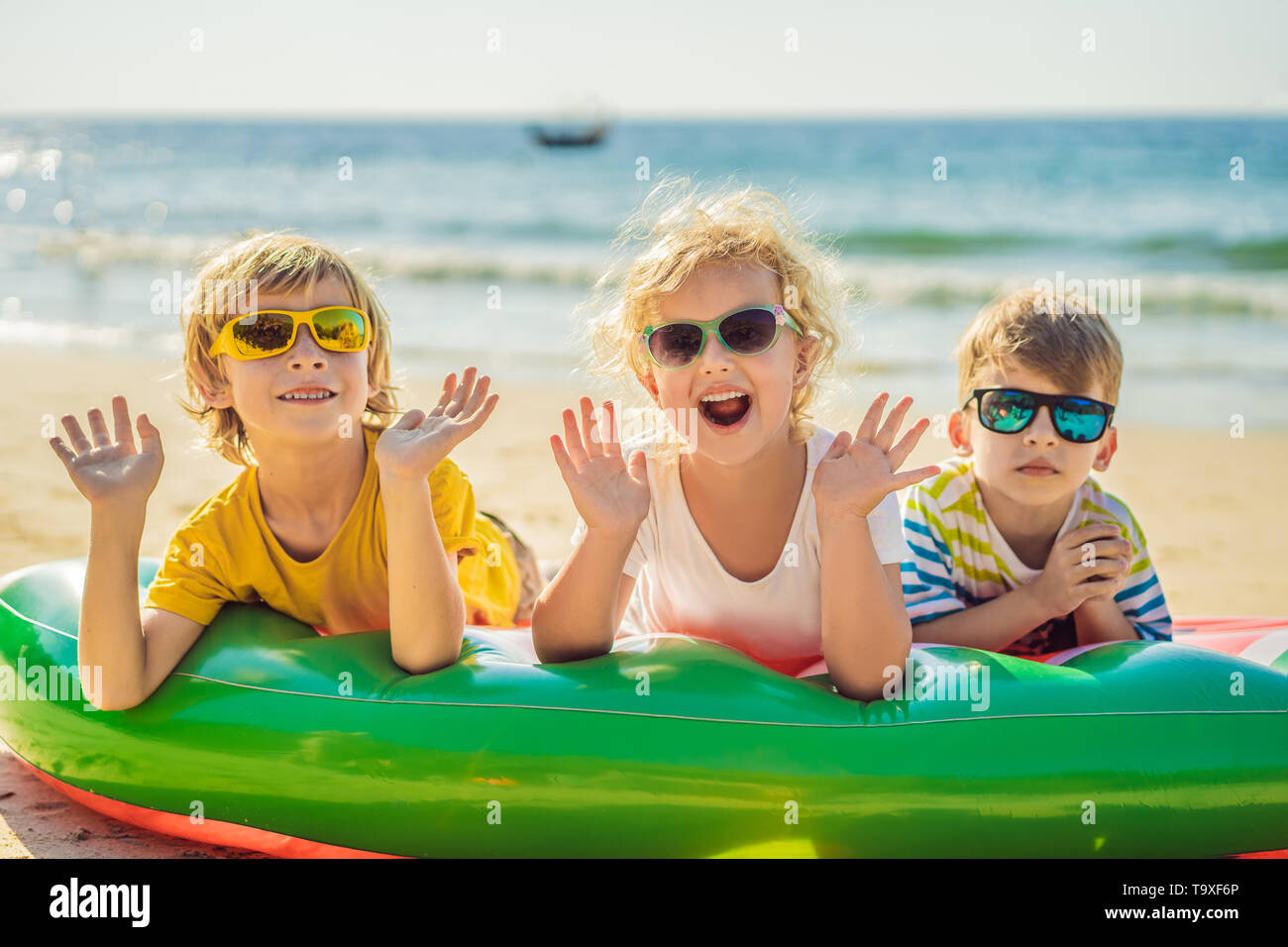 Children sit on an inflatable mattress in sunglasses against the sea and have fun - Stock Image