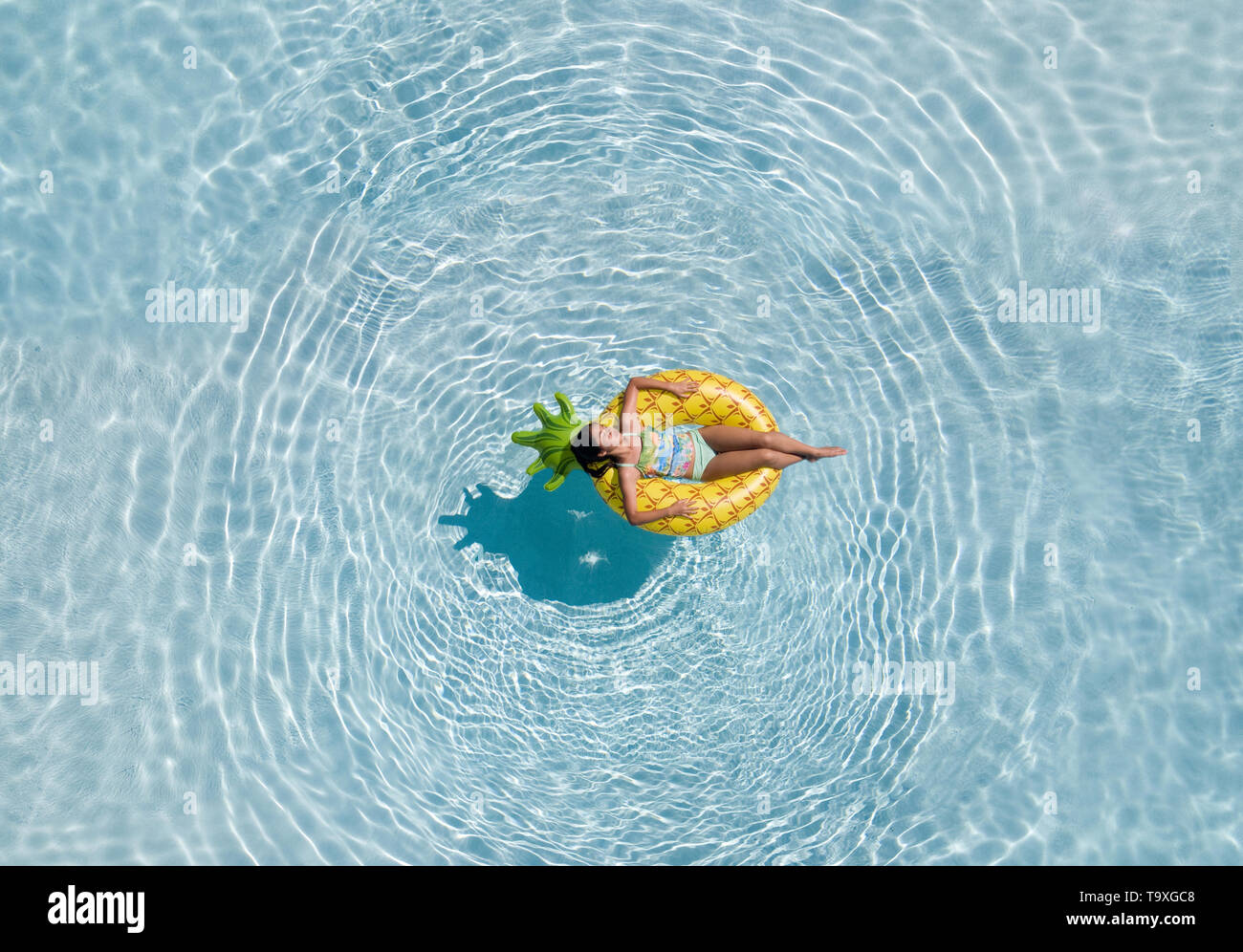 A drone aerial shot of a teenage girl relaxing on a pineapple shaped pool floaty in a swimming pool - Stock Image