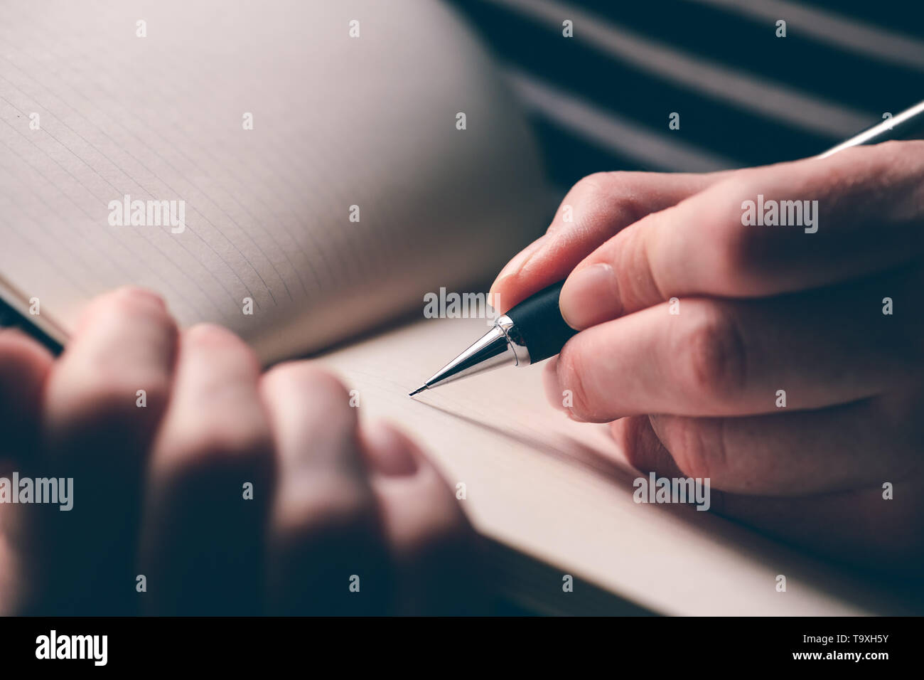 Left-handed woman writing diary, close up of hands with pencil and notebook - Stock Image