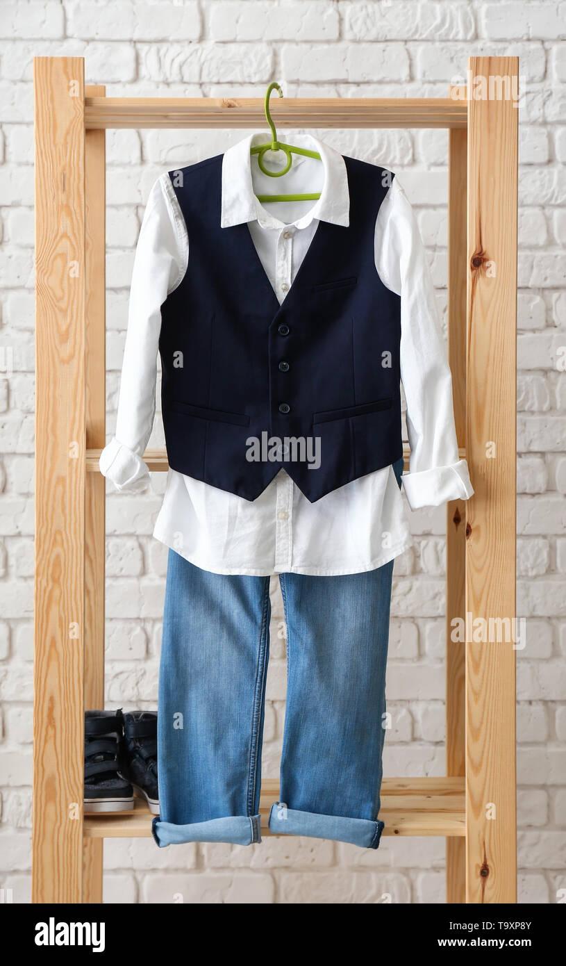 Stylish set of clothes for kid on white brick background - Stock Image