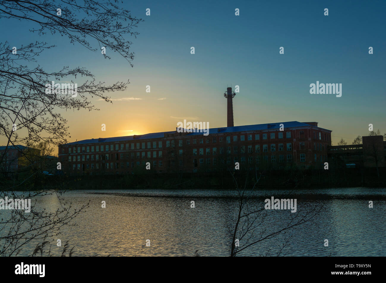 Beautiful sunset on the Knazal lake on the background of a large old weaving factory, the city of Yuzha, Ivanovo region, Russia. - Stock Image