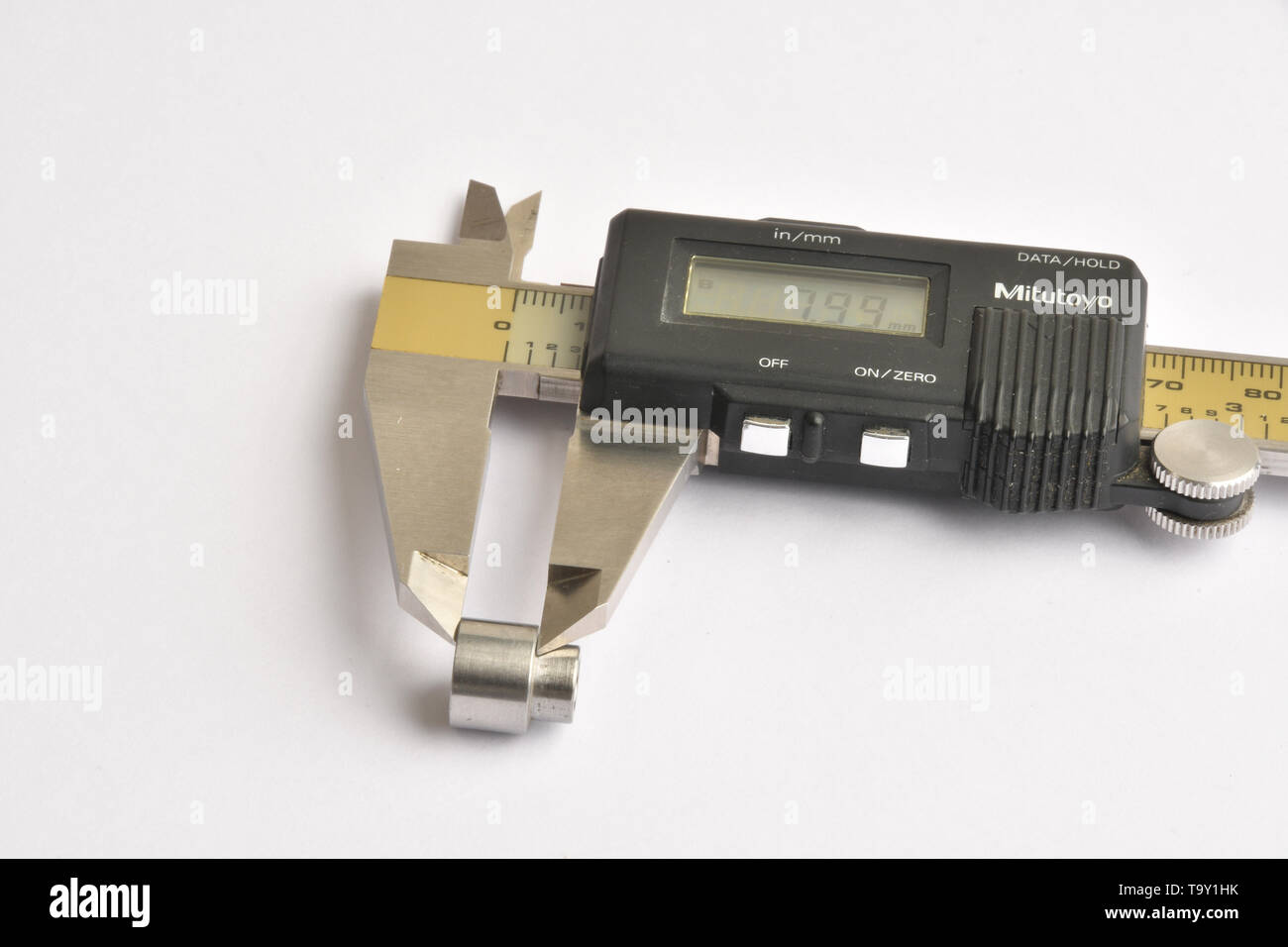Digital vernier caliper measuring the length of a turned component. - Stock Image