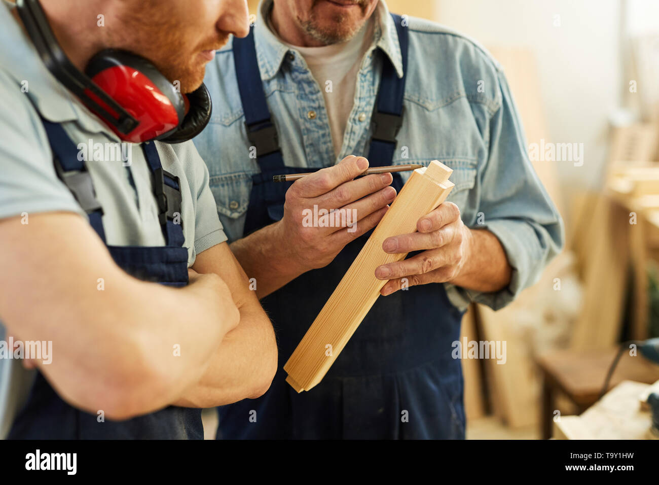 Closeup portrait of senior carpenter teaching apprentice  while working  in joinery workshop, copy space - Stock Image