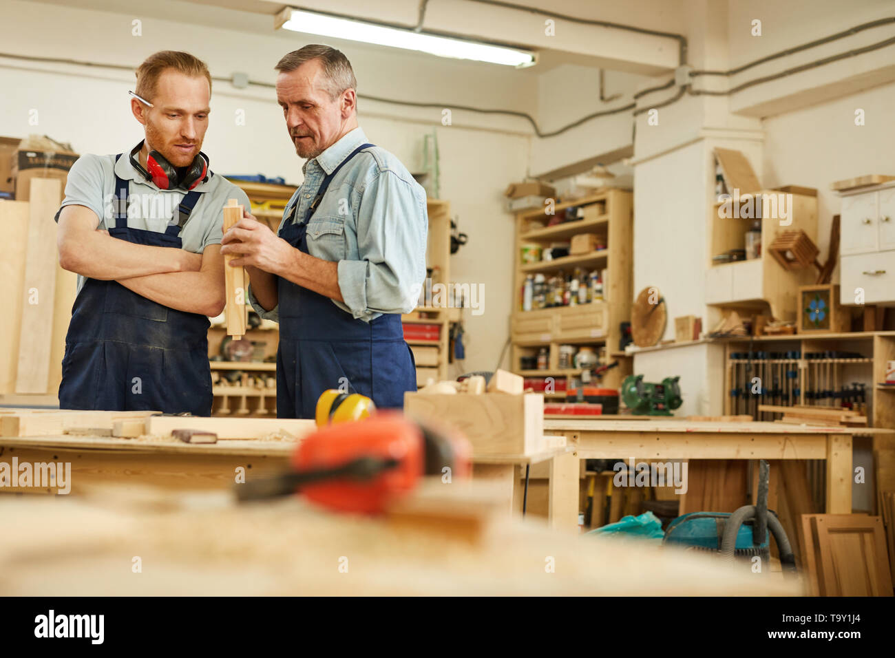 Waist up portrait of senior carpenter teaching apprentice  while working  in joinery workshop, copy space - Stock Image