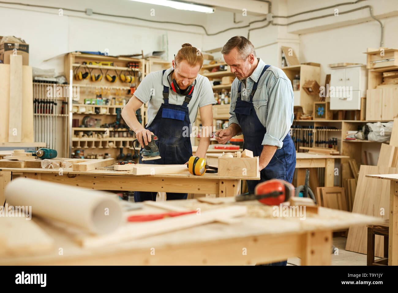 Portrait of senior carpenter teaching apprentice  while working  in joinery workshop, copy space - Stock Image