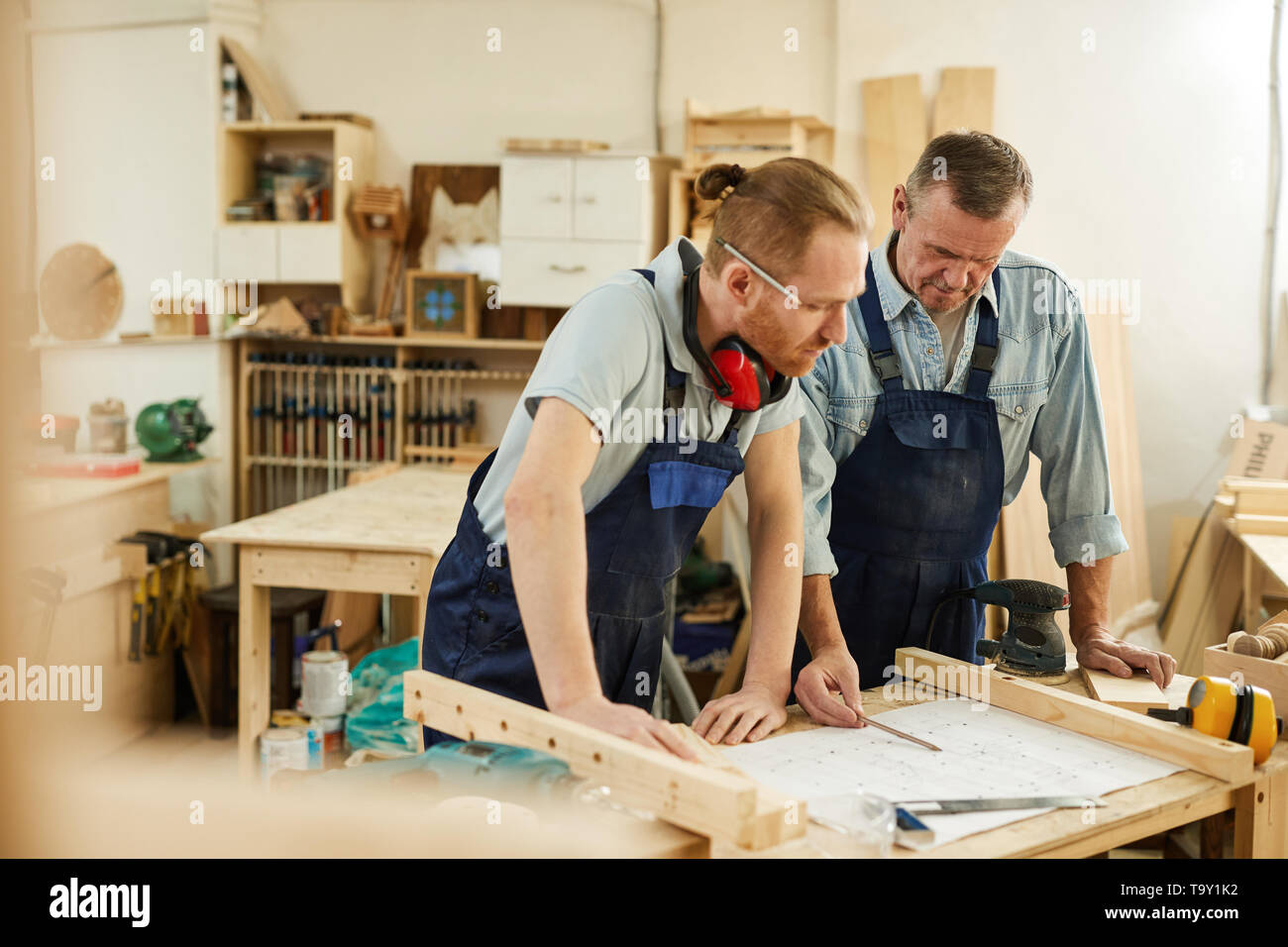 Portrait of senior carpenter teaching apprentice  while working together  in joinery workshop, copy space - Stock Image