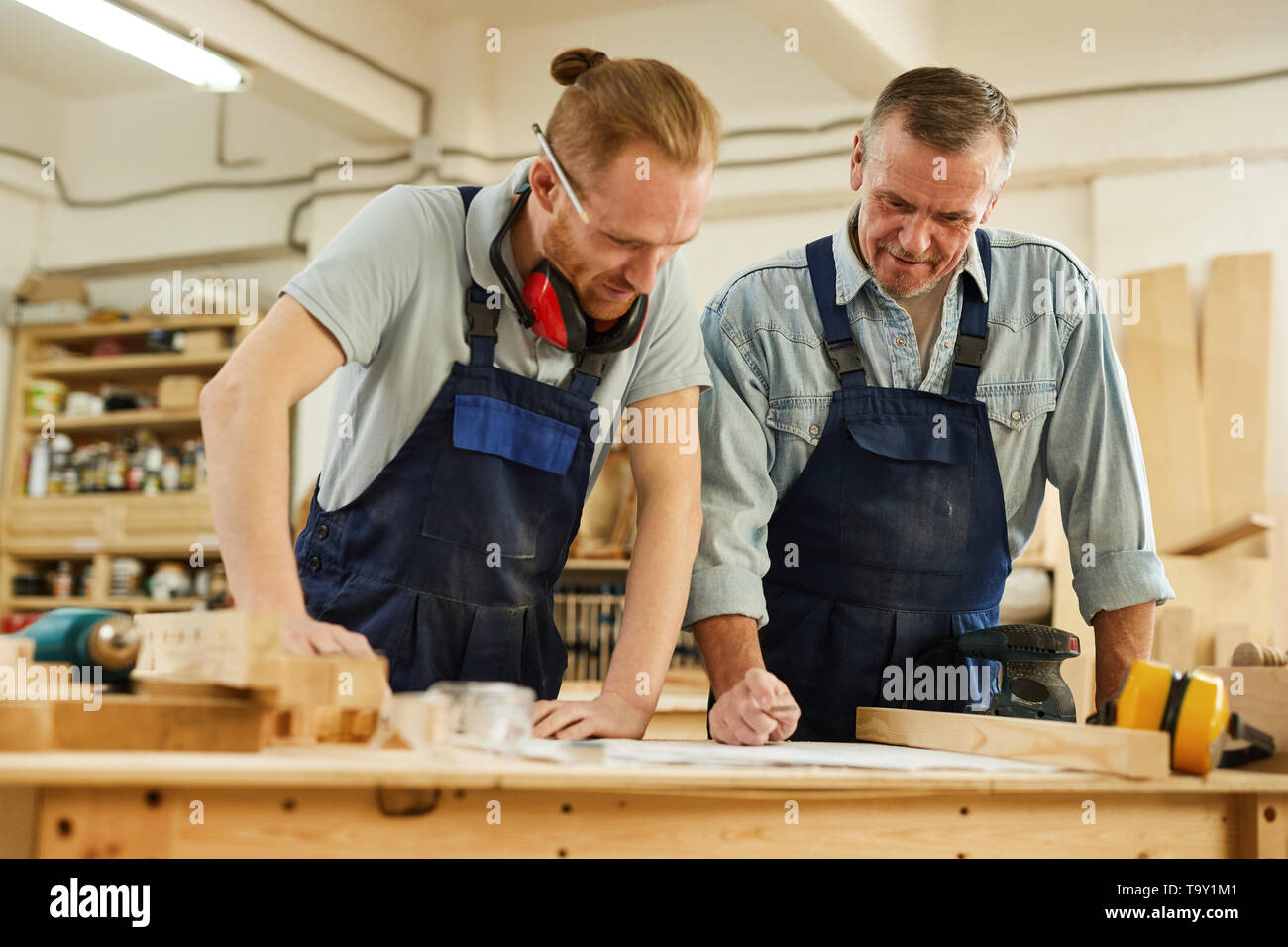 Waist up  portrait of senior carpenter teaching apprentice  while working together  in joinery workshop - Stock Image
