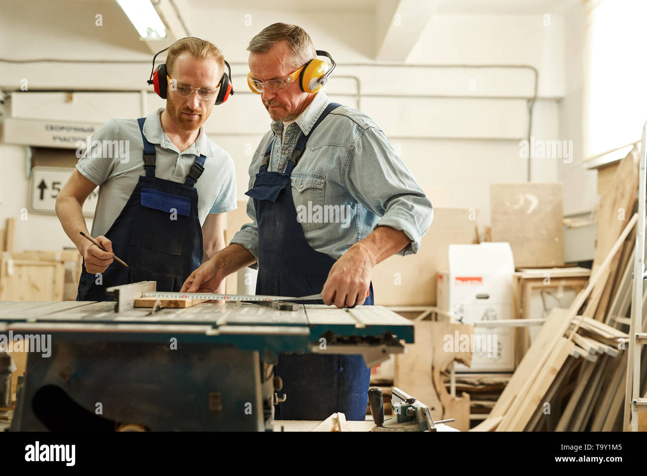 Waist up  portrait of senior carpenter working with apprentice in joinery workshop, copy space - Stock Image