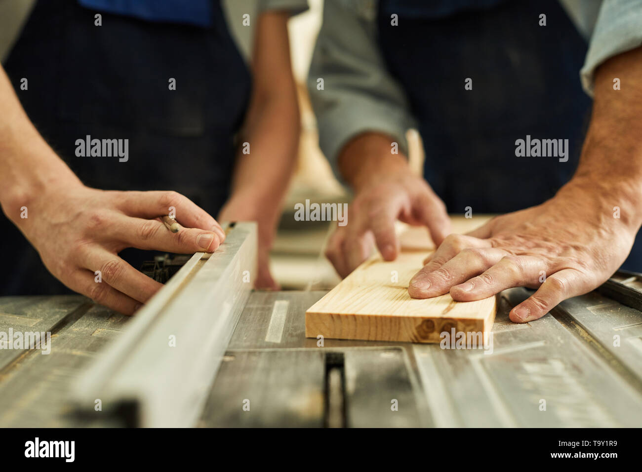 Closeup of senior carpenter working with apprentice in joinery workshop, copy space - Stock Image