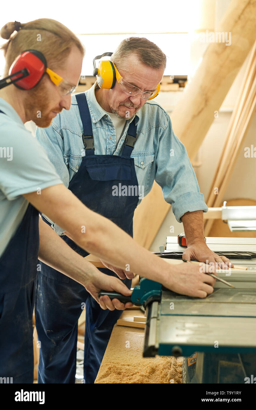 Side view  portrait of senior carpenter working with apprentice in joinery workshop - Stock Image