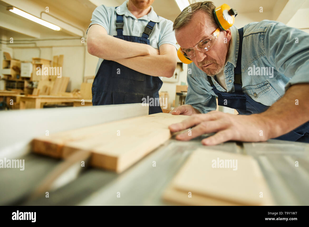Portrait of  carpenter cutting wood using disksaw while working in joinery workshop, copy space - Stock Image