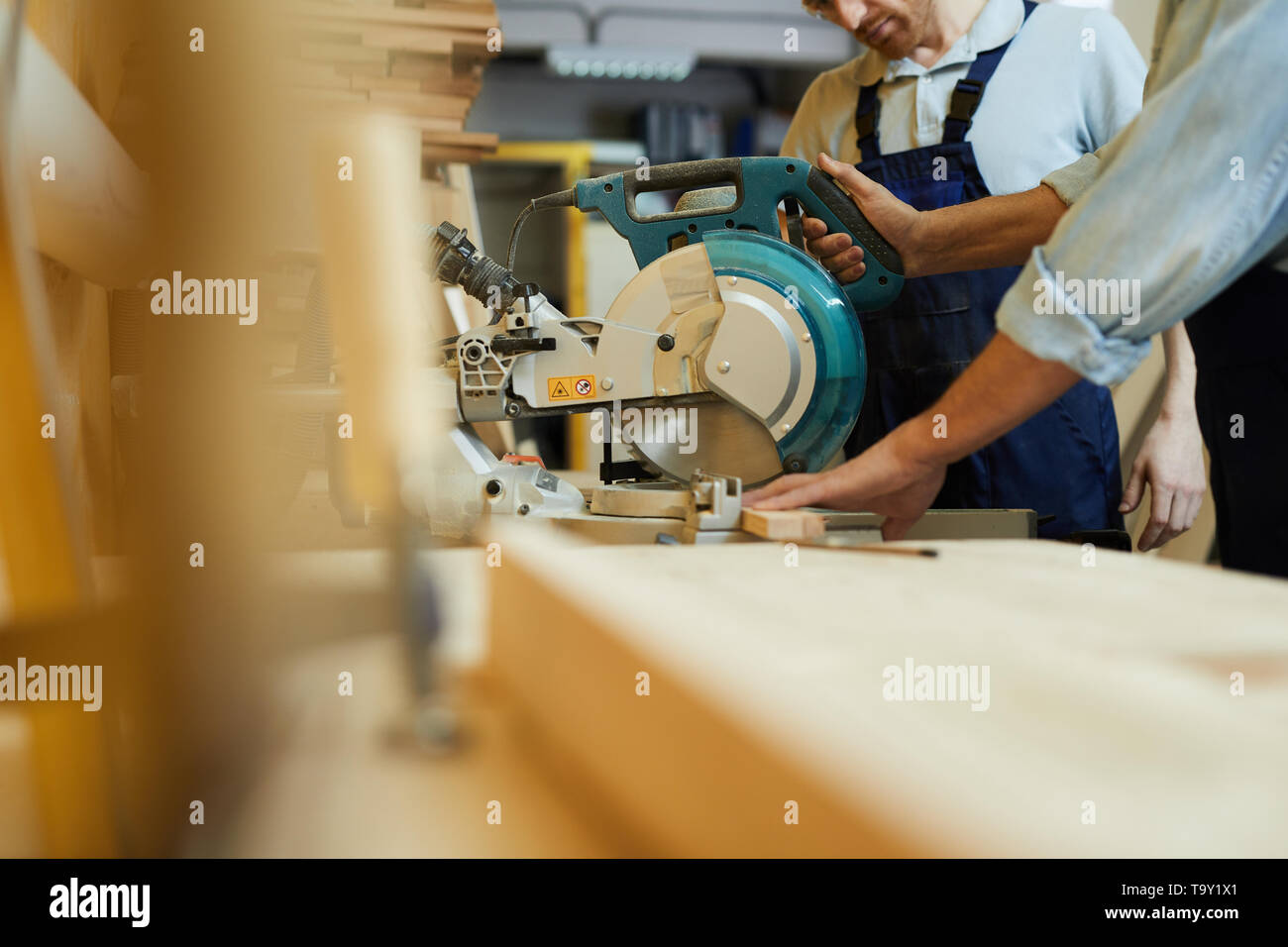 Side view closeup of  carpenter cutting wood using disksaw while working in joinery, copy space - Stock Image