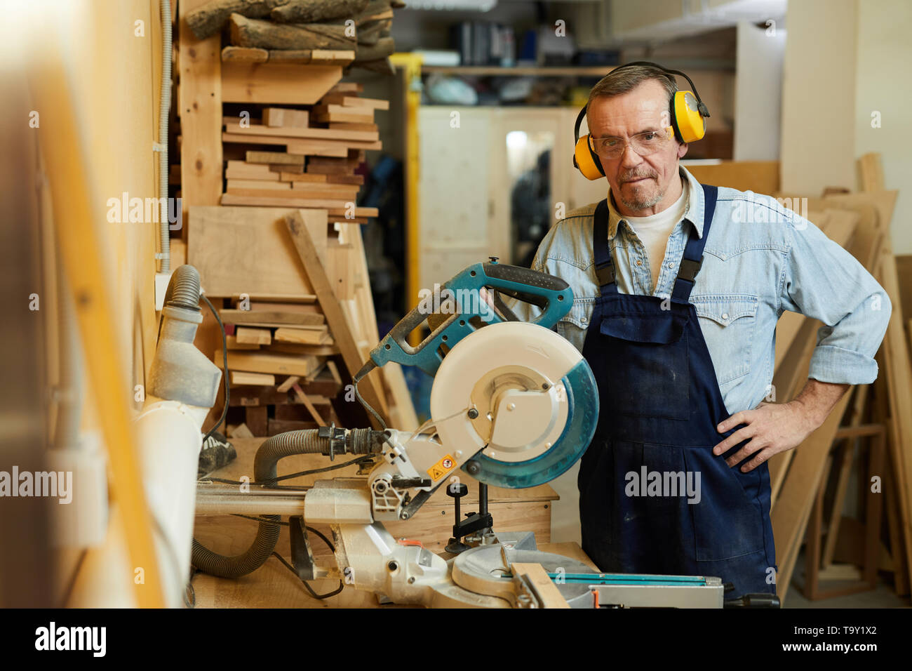 Waist up portrait of senior carpenter posing standing by disksawwhile working in joinery, copy space - Stock Image