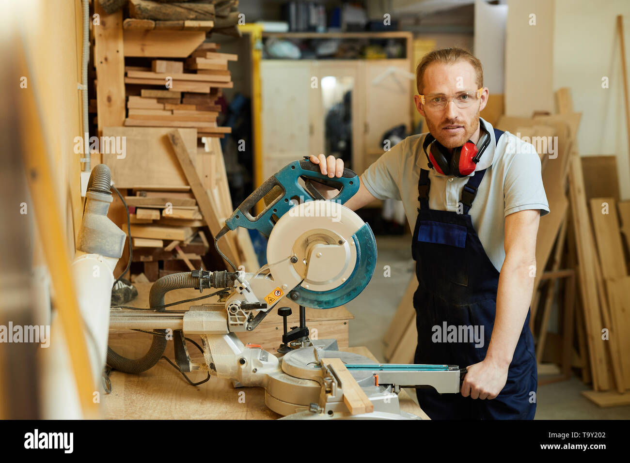Waist up portrait of carpenter looking at camera while standing by disksaw in joinery, copy space - Stock Image