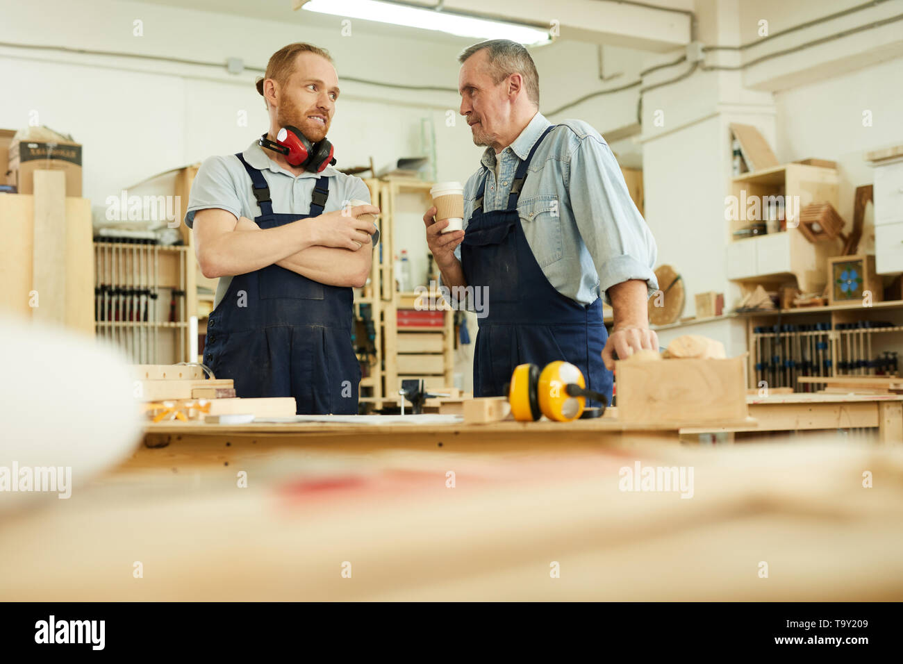 Waist up portrait of two carpenters drinking coffee during break standing in joinery workshop, copy space - Stock Image
