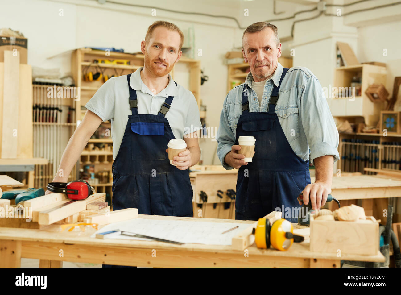 Waist up portrait of two carpenters looking at camera while standing in joinery workshop, copy space - Stock Image