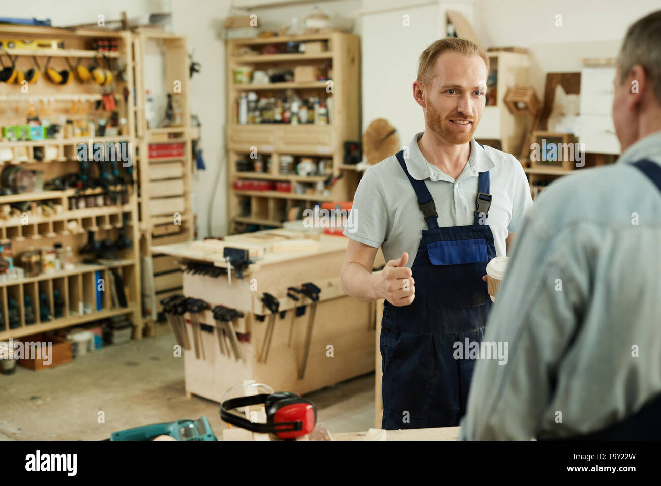 Portrait of young carpenter talking to senior worker during coffee break in workshop, copy space - Stock Image
