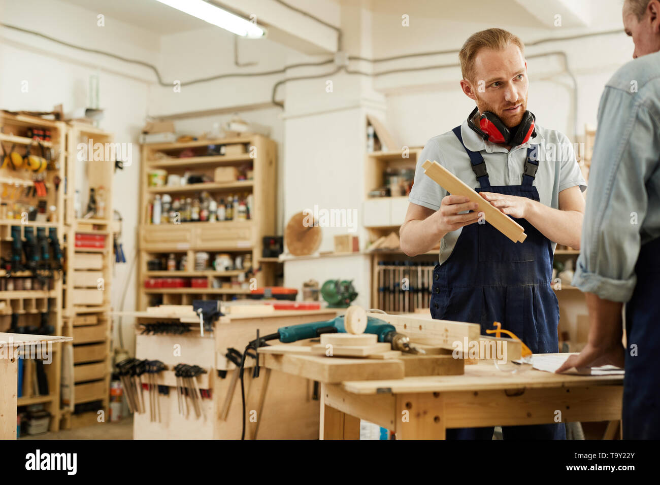 Portrait of young carpenter talking to senior worker in workshop, copy space - Stock Image