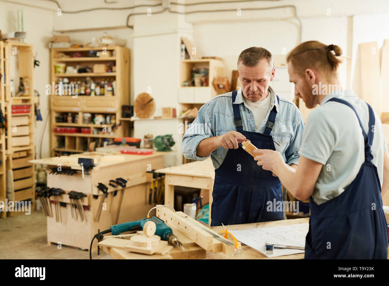 Portrait of senior carpenter helping young trainee while working in joinery workshop, copy space - Stock Image
