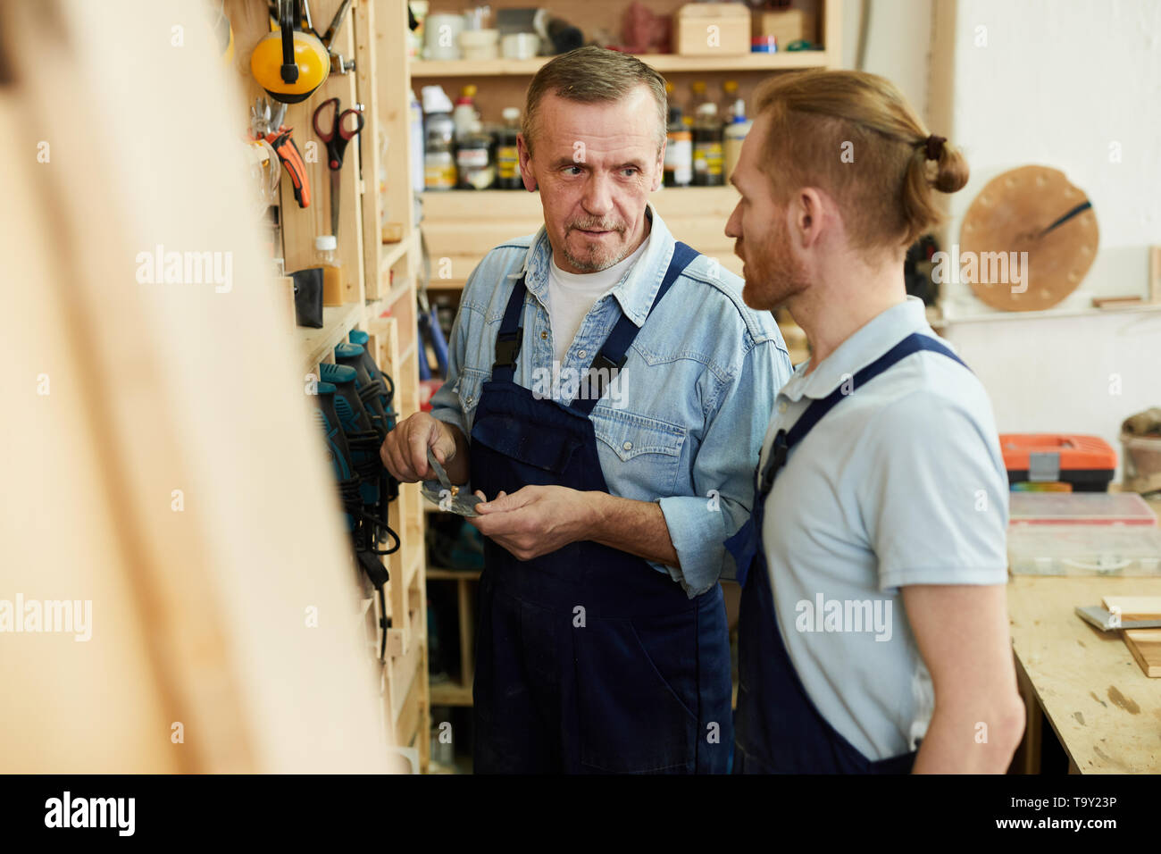 Portrait of senior carpenter talking to young trainee while working in joinery workshop, copy space - Stock Image