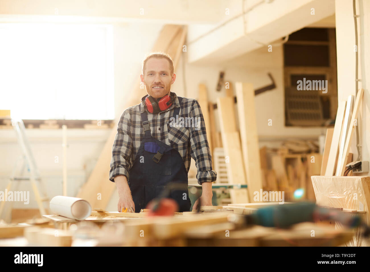 Portrait of red haired carpenter smiling at camera while working in joinery lit by sunlight, copy space - Stock Image