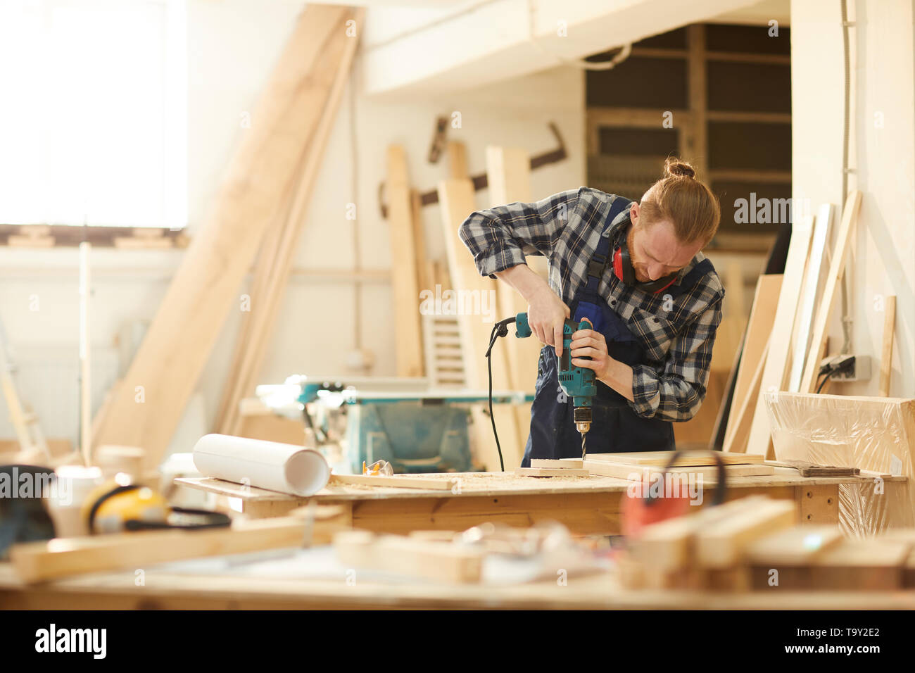 Waist up portrait of red haired carpenter working in joinery lit by sunlight, copy space - Stock Image