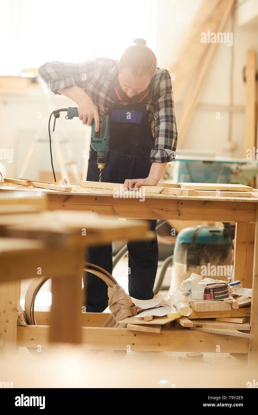 Portrait of red haired carpenter drilling wood while working in joinery lit by sunlight, copy space - Stock Image