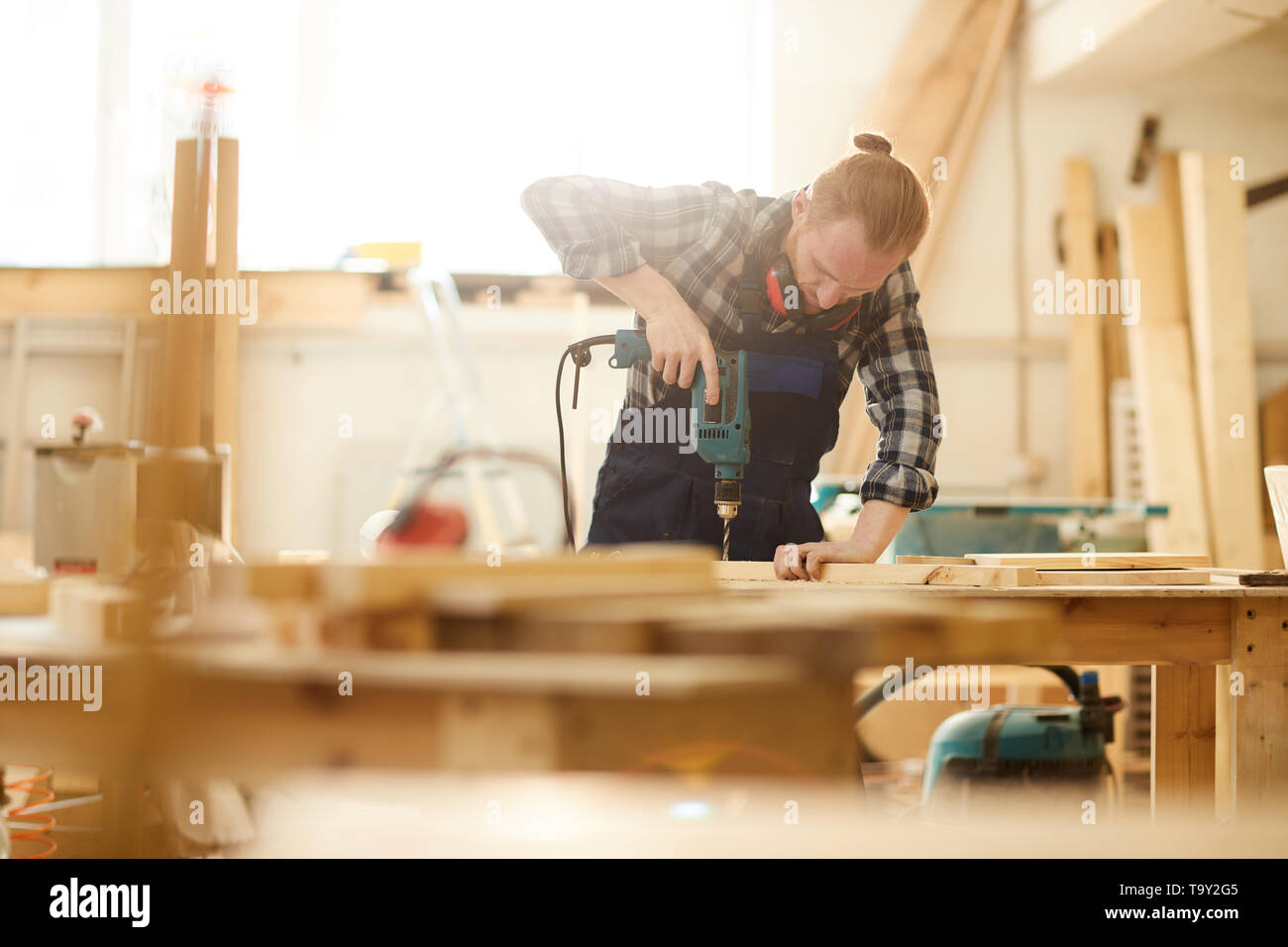 Waist up portrait of red haired carpenter drilling wood while working in joinery lit by sunlight, copy space - Stock Image