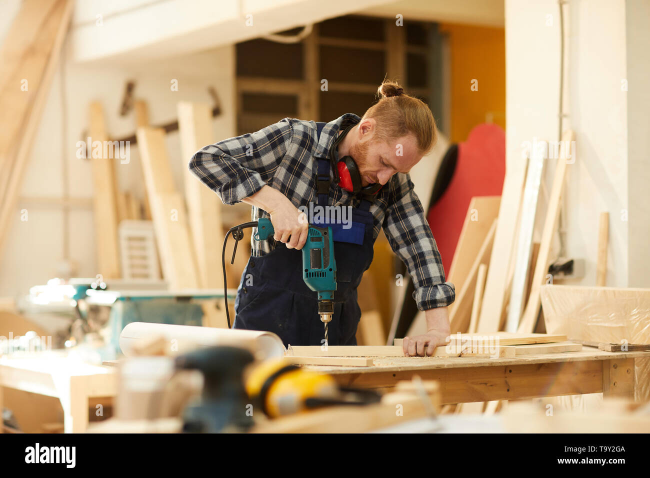 Waist up portrait of modern carpenter drilling wood while working in joinery lit by sunlight, copy space - Stock Image