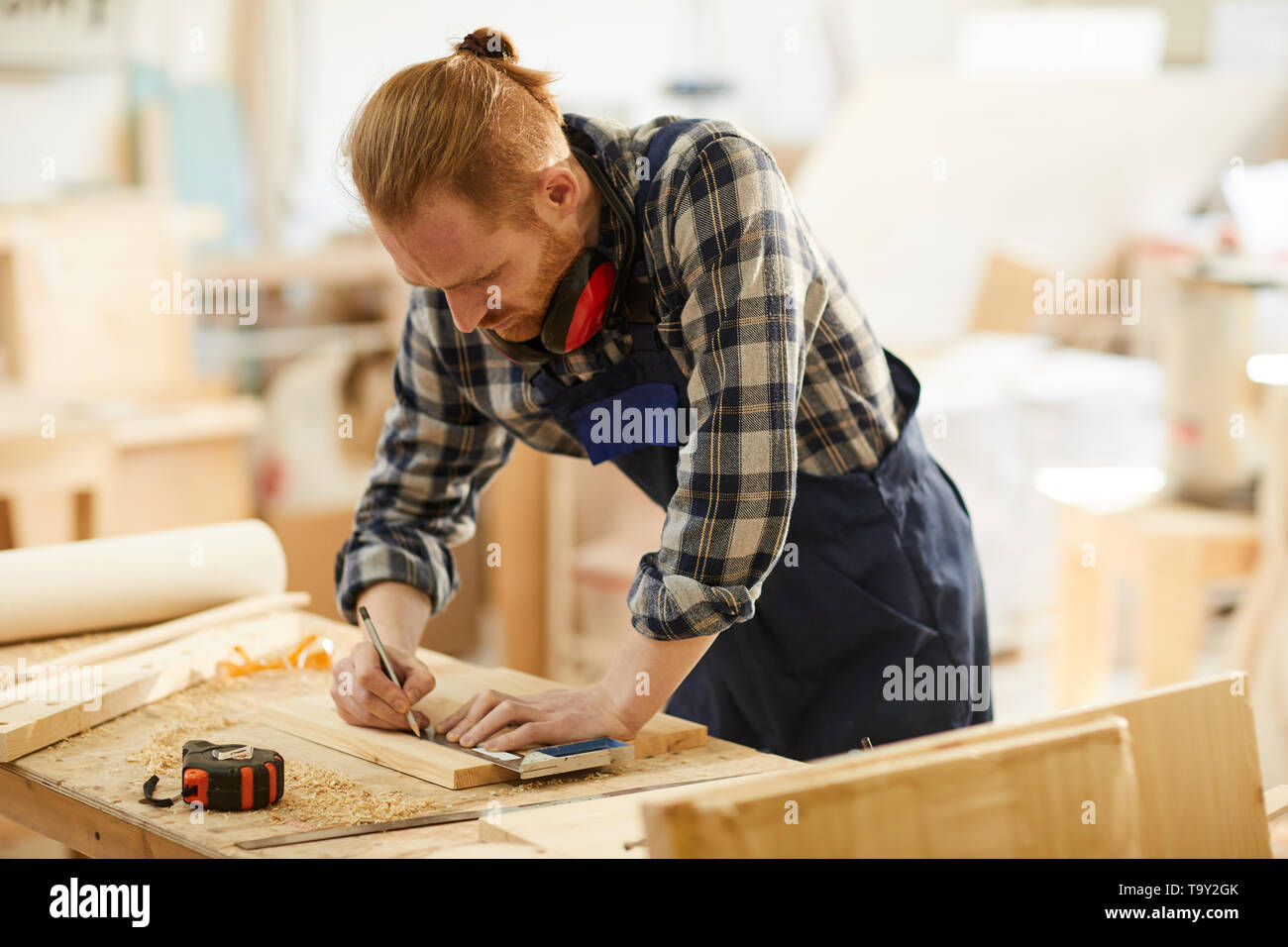 Portrait of modern carpenter marking wood while working in joinery lit by sunlight, copy space - Stock Image
