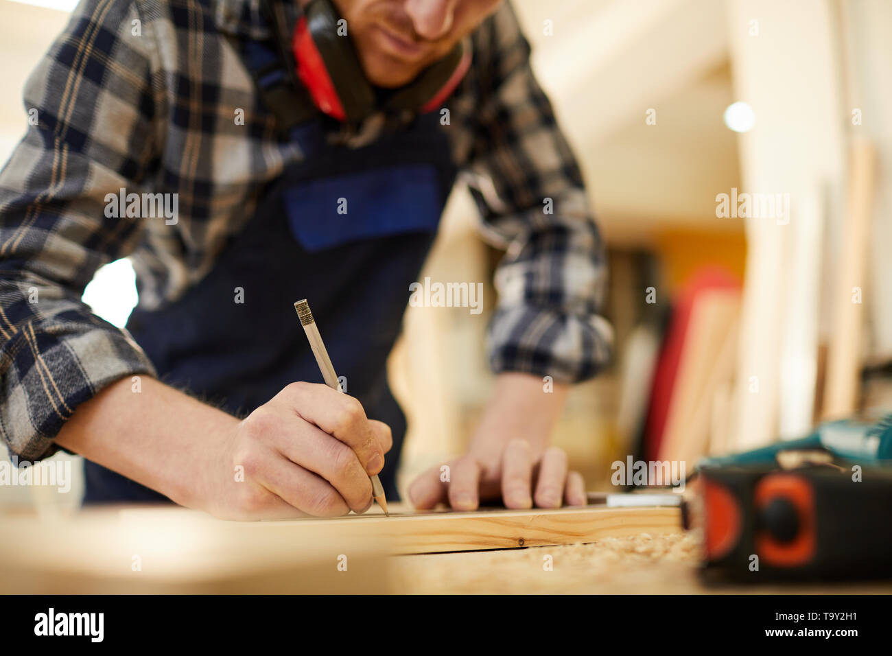 Mid section portrait of modern carpenter marking wood while working in joinery lit by sunlight, copy space - Stock Image