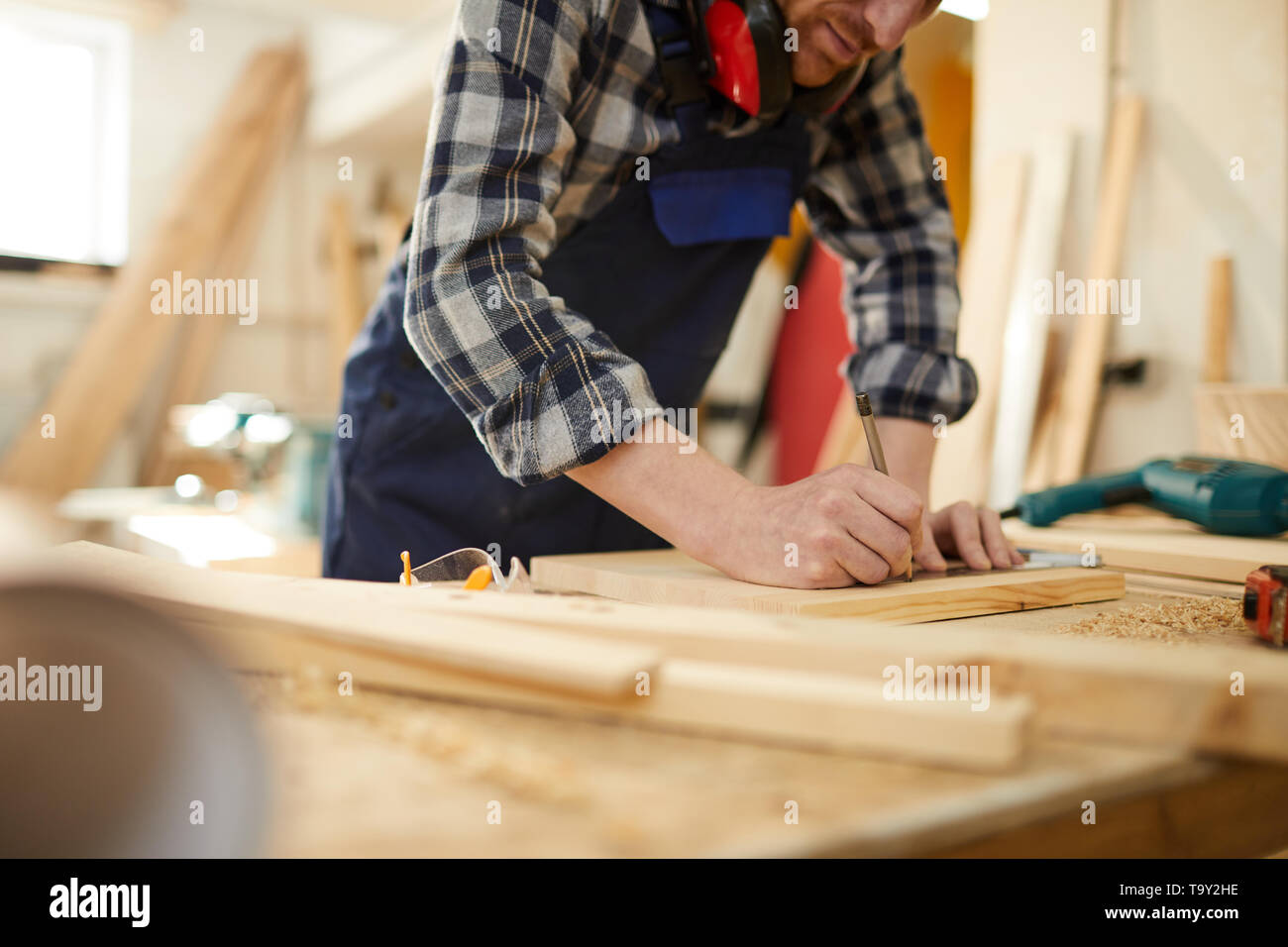 Mid section portrait of unrecognizable carpenter marking wood while working in joinery lit by sunlight, copy space - Stock Image
