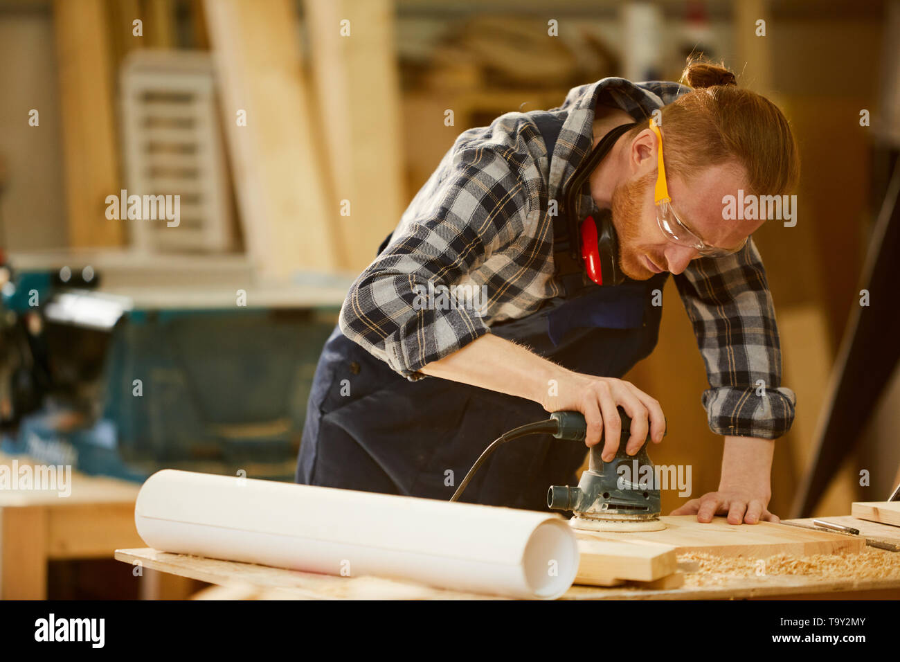 Portrait of contemporary carpenter polishing wood while working in sunlight, copy space - Stock Image