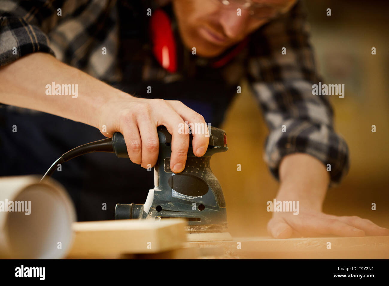 Mid section portrait of contemporary carpenter polishing wood while working in sunlight, copy space - Stock Image