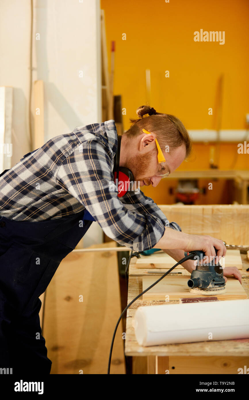 Side view portrait of contemporary carpenter polishing wood while working in sunlight, copy space - Stock Image
