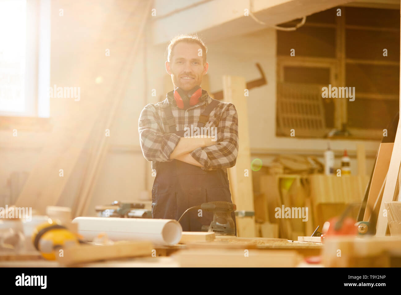 Waist up portrait of contemporary carpenter looking at camera while working in joinery lit by sunlight, copy space - Stock Image