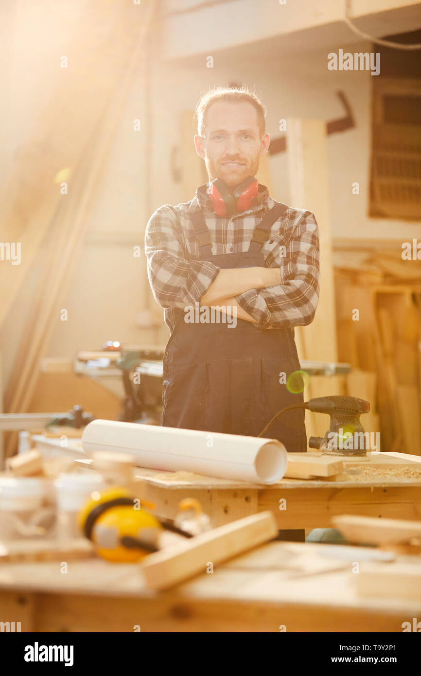Waist up portrait of contemporary carpenter looking at camera while working in joinery lit by sunlight - Stock Image
