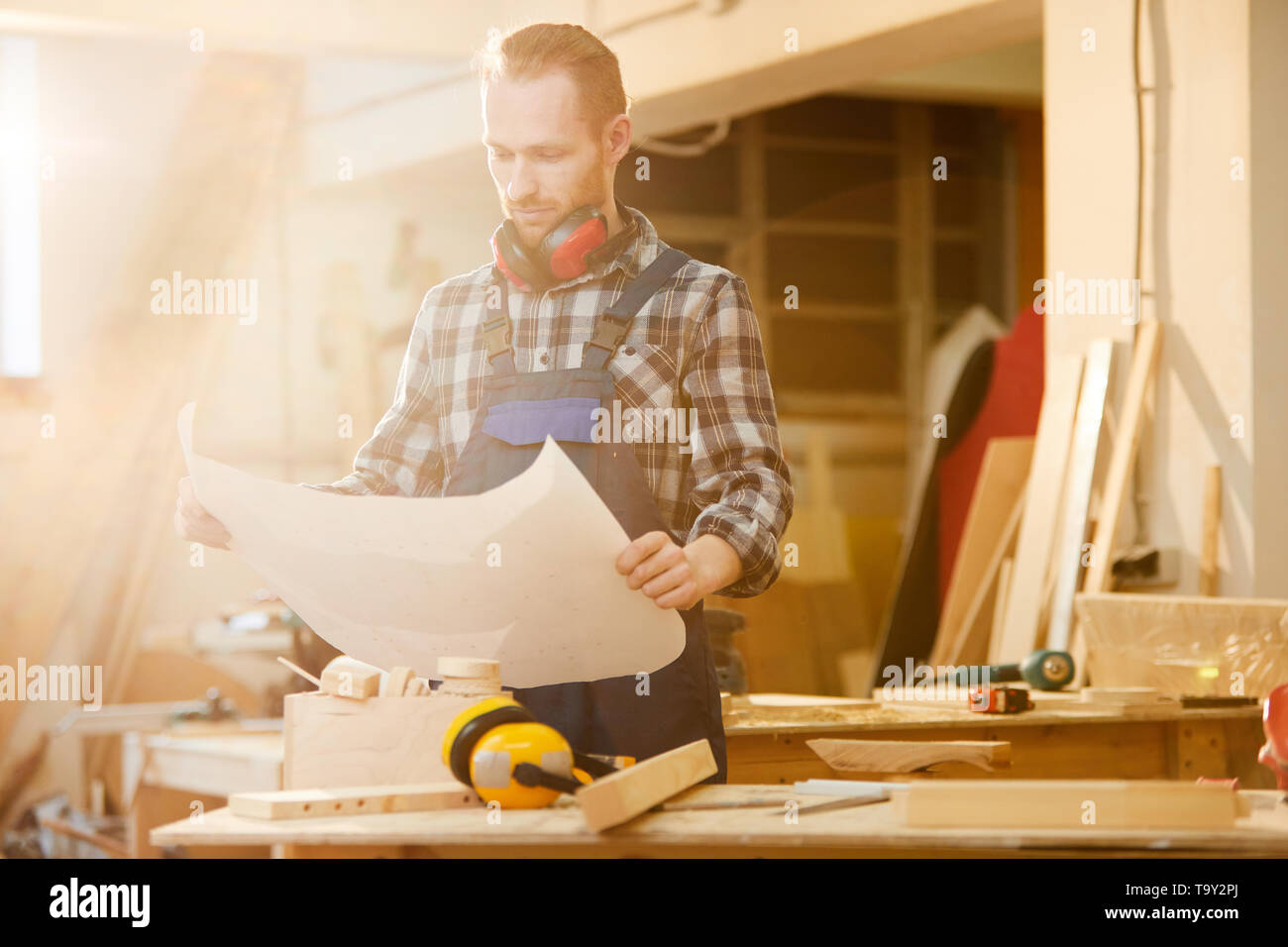 Waist up portrait of contemporary carpenter holding plans while working in joinery lit by sunlight, copy space - Stock Image
