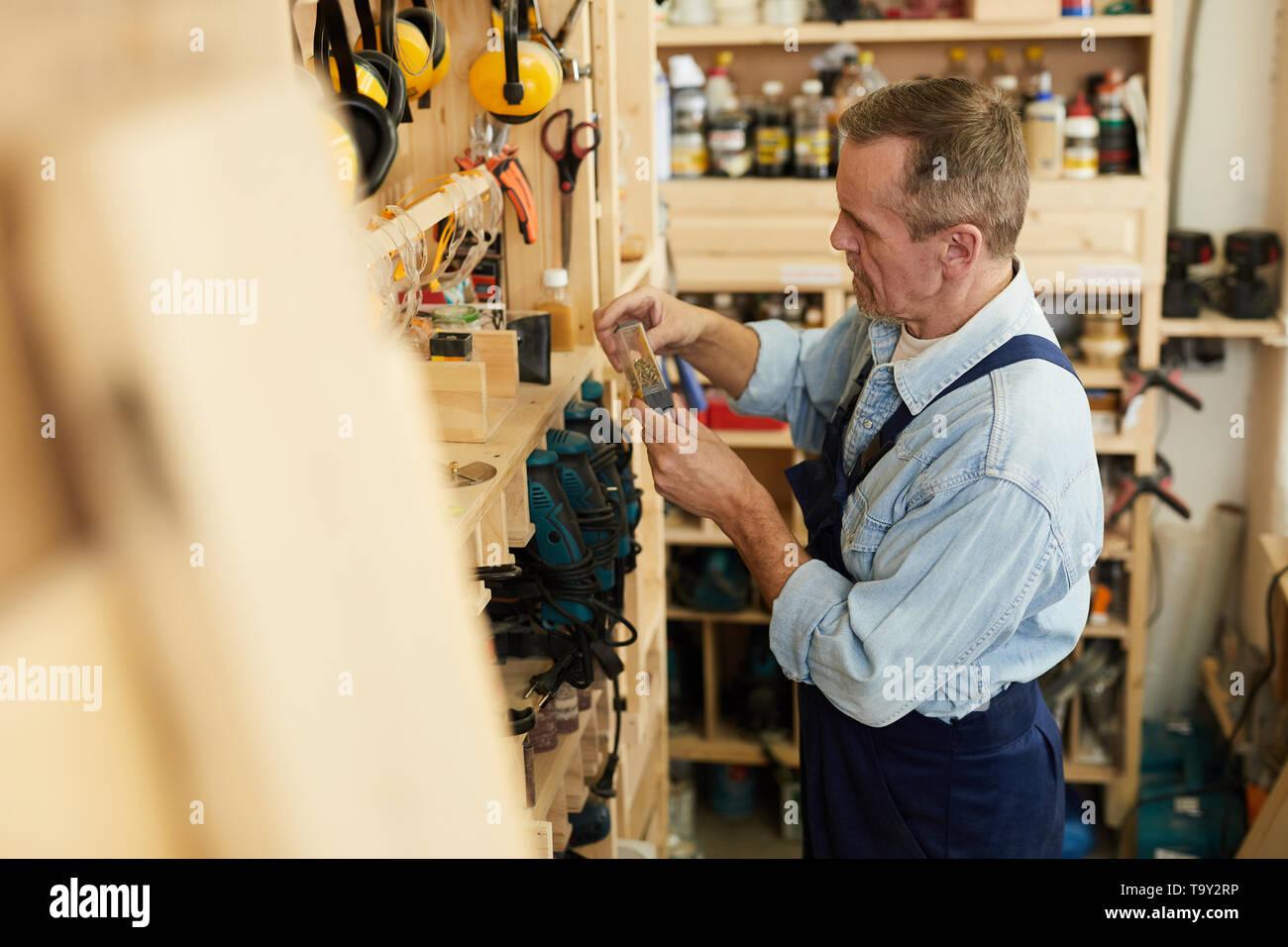 Side view portrait of senior carpenter choosing screws in workshop, copy space - Stock Image