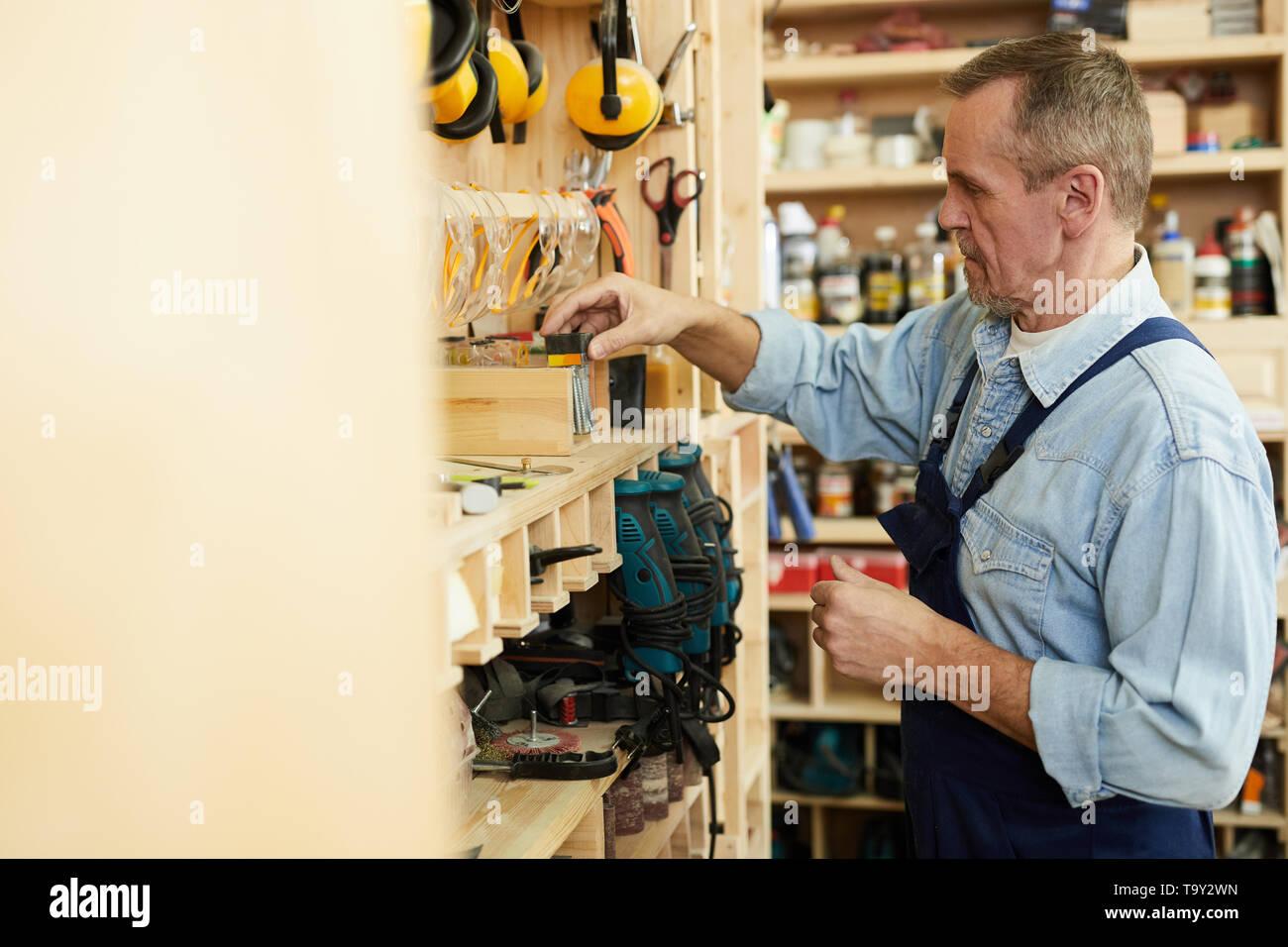 Side view portrait of senior carpenter choosing tools in workshop, copy space - Stock Image