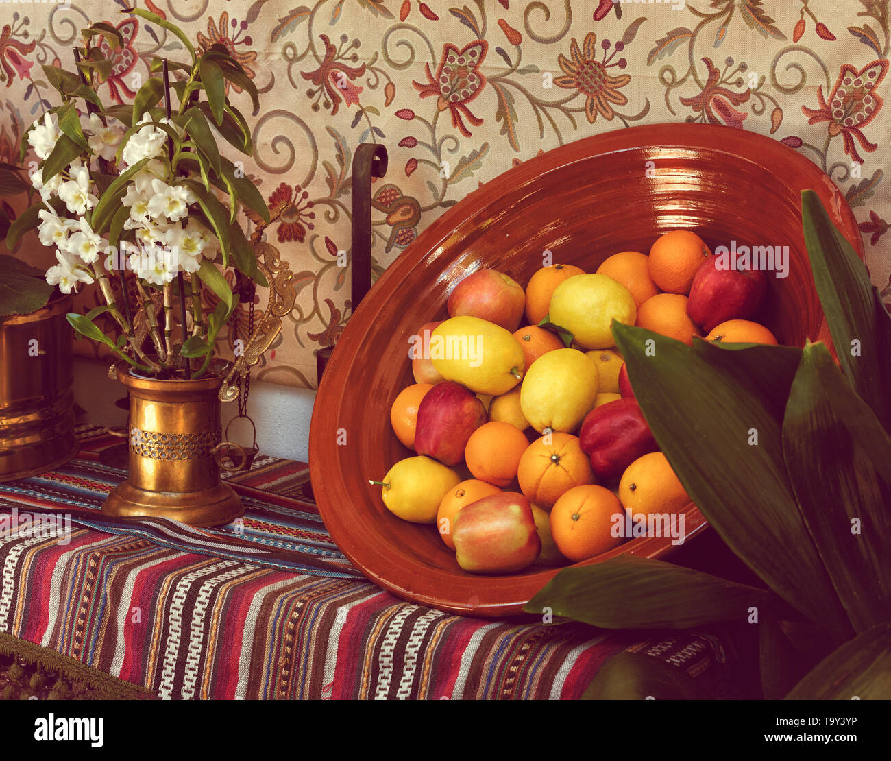 Oranges, apples and lemons in a clay bowl next to a vase with flowers. - Stock Image