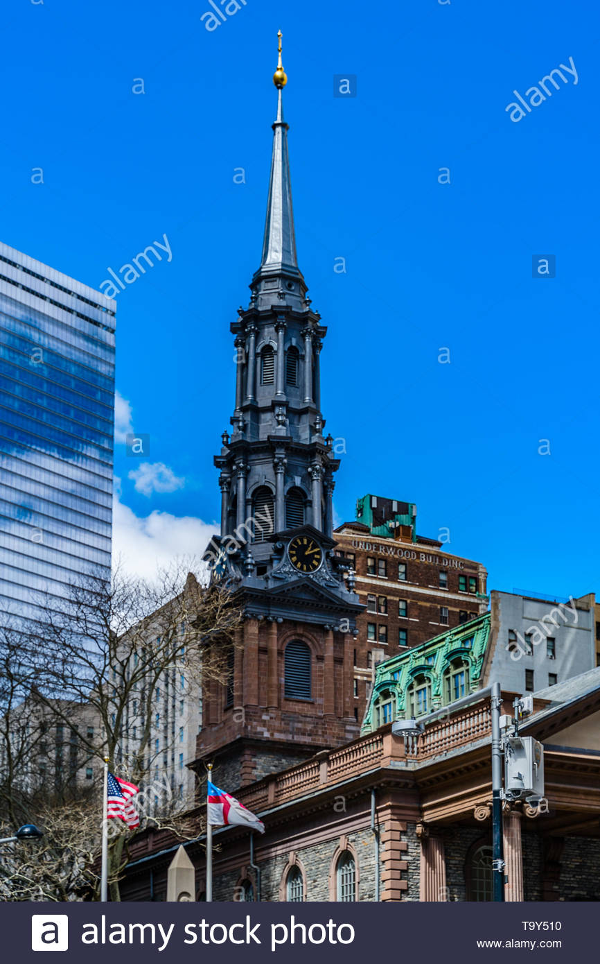 St. Paul's Chapel of Trinity Church Wall Street in the background is Seven World Trade Center with clouds reflected in the windows . - Stock Image