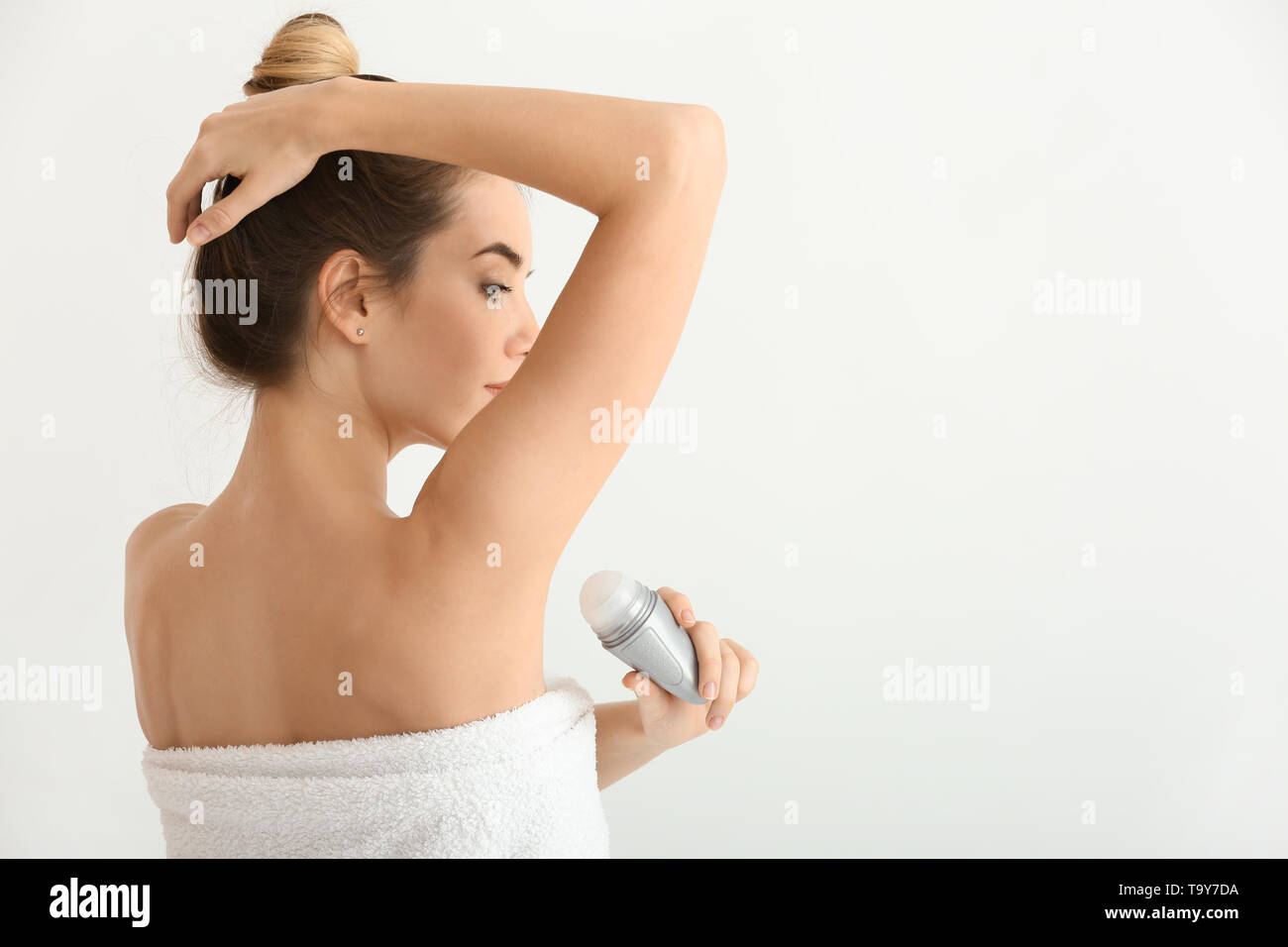 Beautiful young woman with deodorant on light background - Stock Image