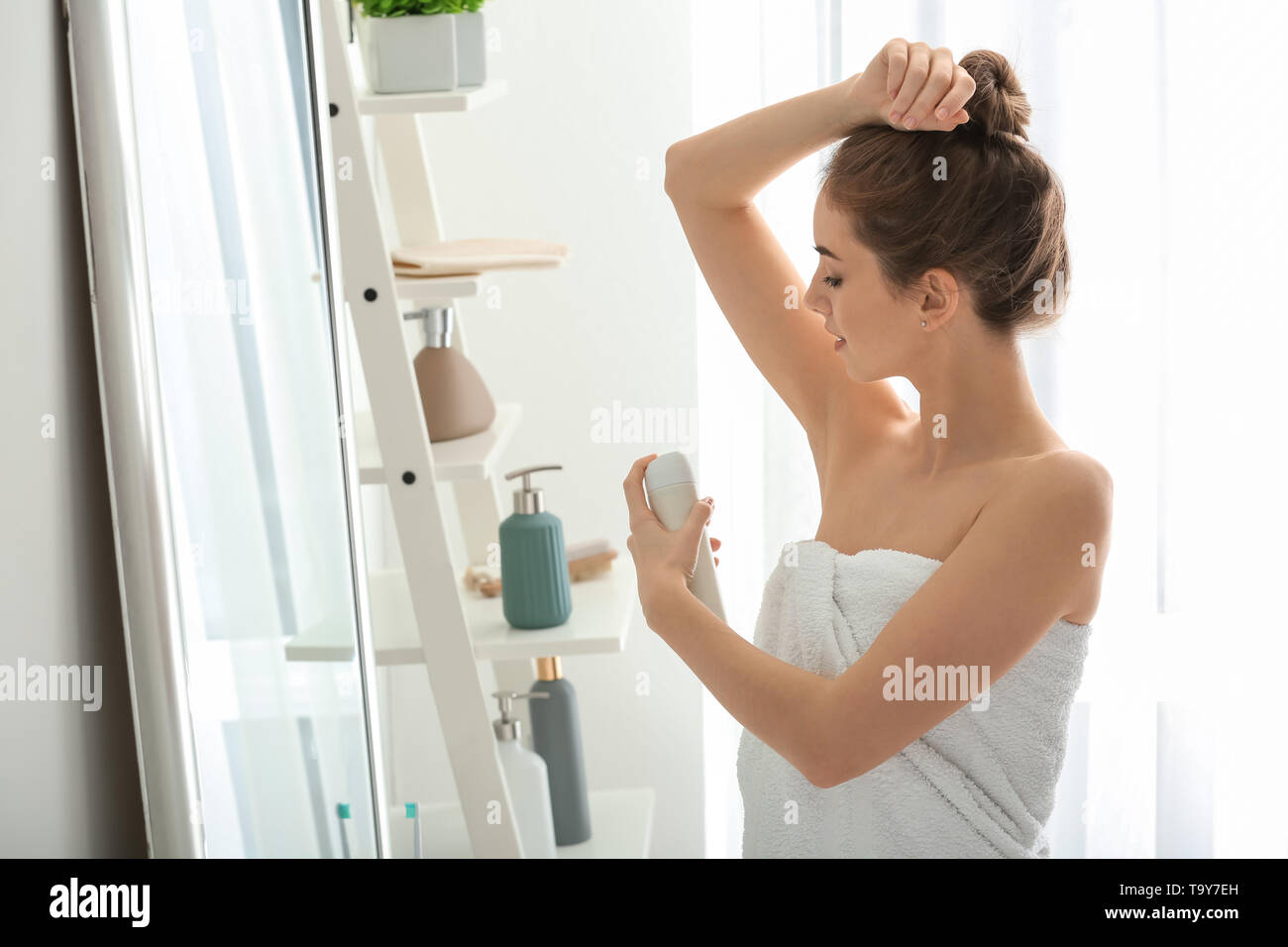 Beautiful young woman with deodorant near mirror in bathroom - Stock Image